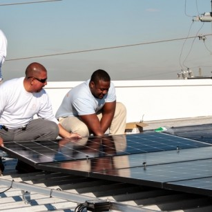 Our crew lead, Robert Sanchez, guiding our solar installers, Clinton Singleton and Jorge Garcia, during an installation.