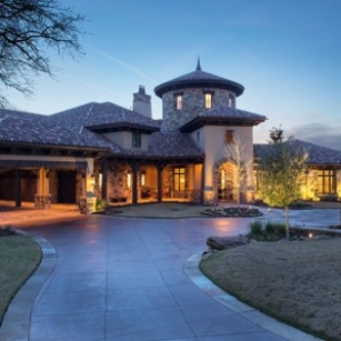 Exterior night shot of Texas lodge inspired home in College Station, Texas.